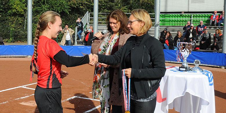 Gonny Farley reikt de medailles uit na het behalen van het landskampioenschap door het U17-team van Red Mosquitos.